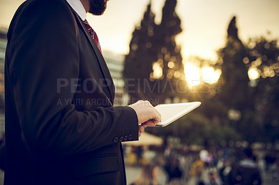 Buy stock photo Cropped shot of an unrecognizable businessman using a digital tablet while standing on a balcony in a foreign city