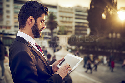 Buy stock photo Cropped shot of a handsome young businessman using a digital tablet while standing on a balcony in a foreign city