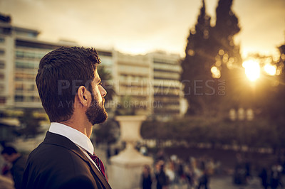 Buy stock photo Cropped shot of a handsome young businessman standing on a balcony in a foreign city