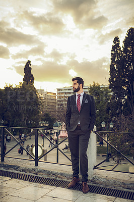 Buy stock photo Full length shot of a handsome young businessman looking thoughtful while standing on a balcony in a foreign city
