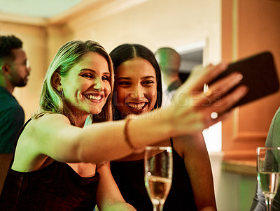 Buy stock photo Cropped shot of two cheerful young women taking a self portrait together inside of a bar at night