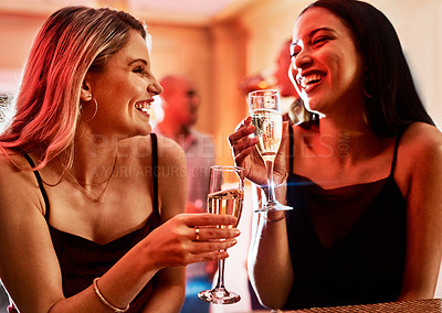 Buy stock photo Cropped shot of two cheerful young women chatting while having drinks inside of a bar at night