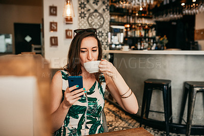 Buy stock photo Cropped shot of an attractive young woman using her cellphone and drinking a cup of coffee in a cafe