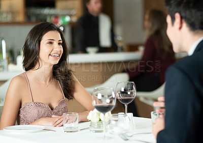 Buy stock photo Shot of a happy young couple enjoying a romantic date at a restaurant