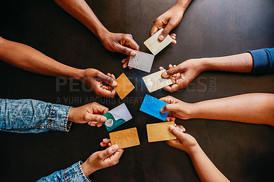 Buy stock photo High angle shot of a group of unrecognizable people holding out their credit cards over a table