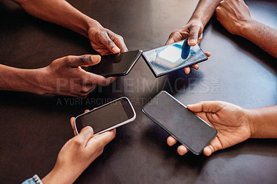 Buy stock photo High angle shot of a group of unrecognizable people holding out their cellphones while browsing over a table