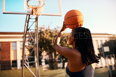 Buy stock photo Full length shot of an unrecognizable sportswoman playing basketball alone during the day