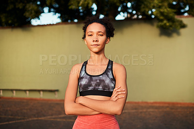 Buy stock photo Cropped shot of an attractive young sportswoman standing alone on the court with her arms folded during the day