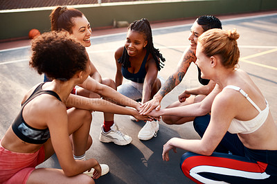 Buy stock photo Cropped shot of a diverse group of sportswomen piling their hands together before playing basketball during the day