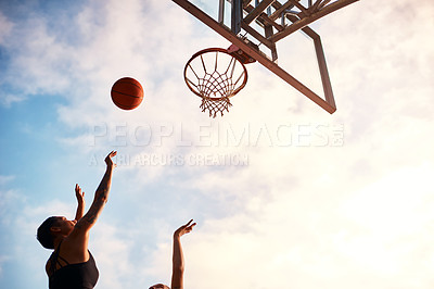 Buy stock photo Cropped shot of an unrecognizable sportswoman blocking her opponent during a basketball game during the day