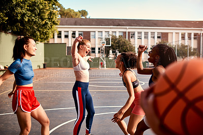 Buy stock photo Cropped shot of a diverse group of sportwomen celebrating their win together after playing basketball