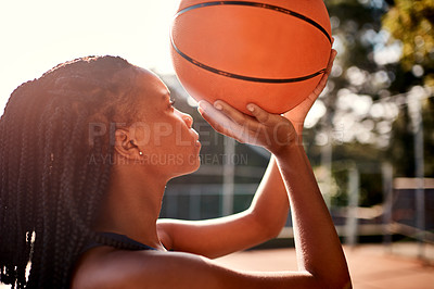 Buy stock photo Cropped shot of an attractive young sportswoman standing on the court alone and holding a basketball during the day