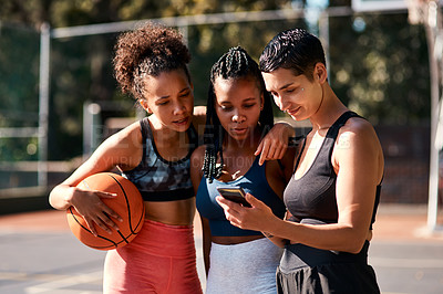 Buy stock photo Cropped shot of a diverse group of sportswomen standing together after playing basketball and looking at a cellphone