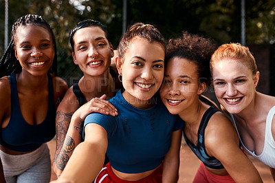 Buy stock photo Cropped shot of a diverse group of sportswomen bonding after a basketball game together during the day