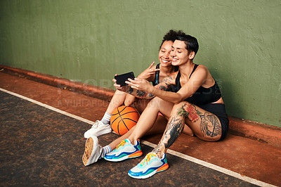 Buy stock photo Cropped shot of two attractive sportswomen sitting together for a selfie after a basketball game during the day