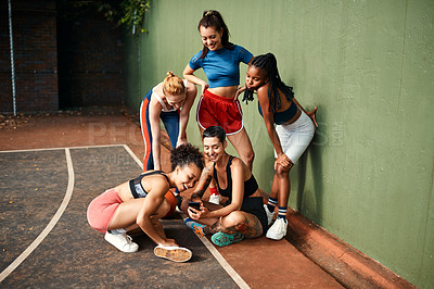 Buy stock photo Cropped shot of a diverse group of sportswomen sitting together for a selfie after a basketball game during the day