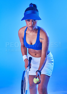 Buy stock photo Cropped portrait of an attractive young female tennis player getting ready to serve against a blue background