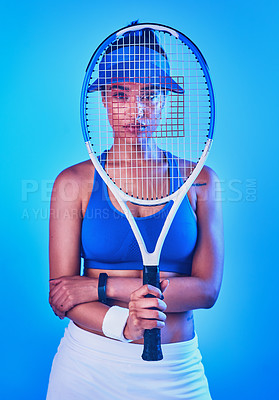 Buy stock photo Cropped portrait of an attractive young female tennis player posing against a blue background