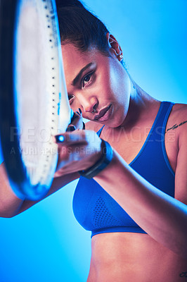 Buy stock photo Cropped shot of an attractive young female tennis player posing against a blue background