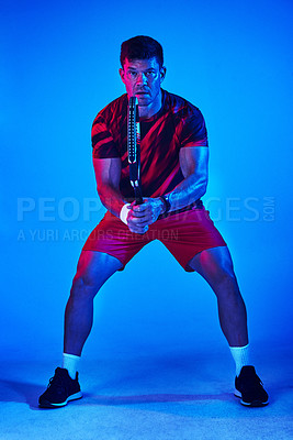 Buy stock photo Blue filtered shot of a man posing with a tennis racket in the studio