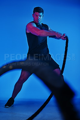 Buy stock photo Blue filtered shot of a man working out with battle ropes in the studio