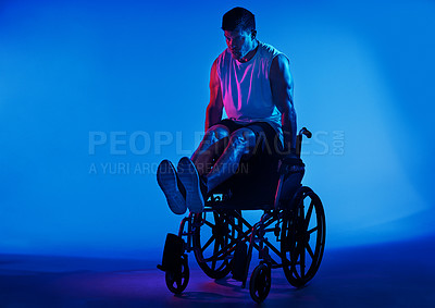 Buy stock photo Blue filtered shot of a man exercising while sitting in his wheelchair