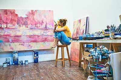 Buy stock photo Shot of a young woman sitting on a stool while looking at a painting in an art studio