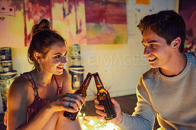 Buy stock photo Cropped shot of a cheerful young couple having a celebratory toast with beer while having a date surrounded by candles and paintings inside of an art studio