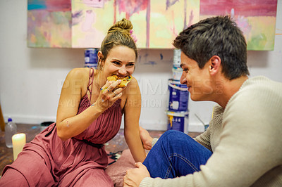Buy stock photo Cropped shot of a cheerful young couple eating pizza together being on a date in an art studio