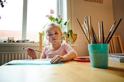 Buy stock photo Portrait of a focused little girl painting a picture with paint brushes while being seated at a table inside during the day