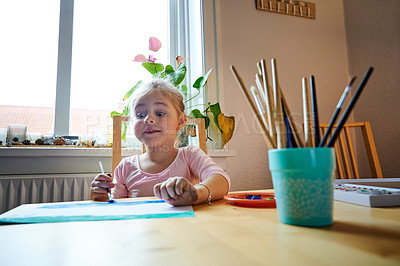 Buy stock photo Cropped shot of a focused little girl painting a picture with paint brushes while being seated at a table inside during the day