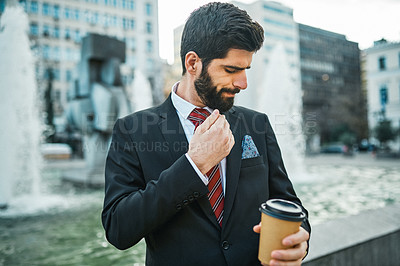 Buy stock photo Shot of a young businessman holding a cup of coffee while out in the city