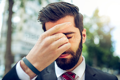 Buy stock photo Shot of a young businessman rubbing his eyes while out in the city