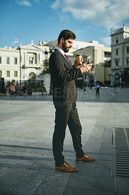 Buy stock photo Shot of a young businessman using a cellphone while holding a cup coffee in the city