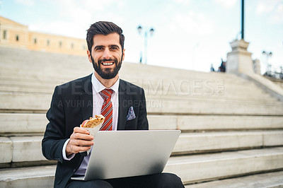 Buy stock photo Portrait of a young businessman eating a pita sandwich while using a laptop in the city