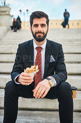 Buy stock photo Portrait of a young businessman eating a pita sandwich while sitting on a staircase in the city