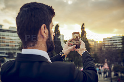 Buy stock photo Cropped shot of a handsome young businessman taking a picture of the view while standing on a balcony in a foreign city