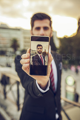 Buy stock photo Cropped portrait of a handsome young businessman taking a selfie while standing on a balcony in a foreign city