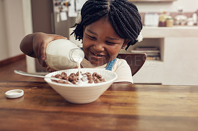 Buy stock photo Cropped shot of an adorable little girl pouring milk into her cereal bowl at home