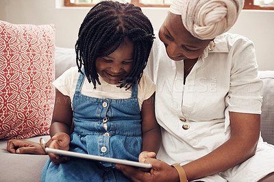 Buy stock photo Cropped shot of an adorable little girl using a digital tablet while bonding with her mother at home