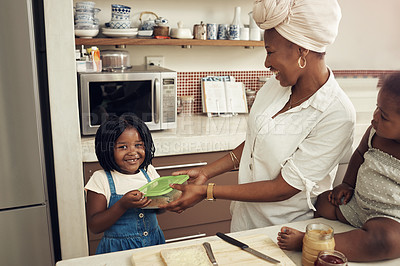 Buy stock photo Cropped shot of a young mother preparing a healthy meal for her two young daughters at home
