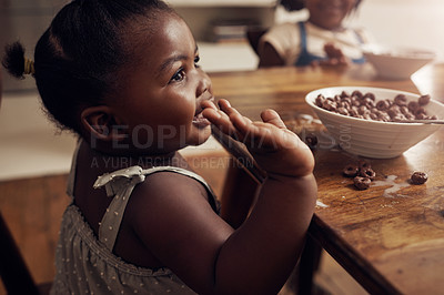 Buy stock photo Cropped shot of an adorable baby girl eating cereal at home with her elder sister in the background