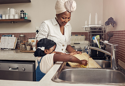 Buy stock photo Cropped shot of an adorable little girl helping her mother do the dishes at home