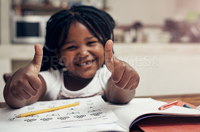 Buy stock photo Portrait of an adorable little girl posing with her thumbs up while doing her homework at home