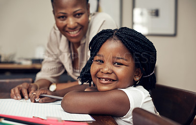 Buy stock photo Portrait of an adorable little girl smiling while doing her homework with her mother at home