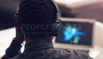 Buy stock photo Rearview shot of an unrecognizable businessman using a laptop while wearing headphones in a modern office