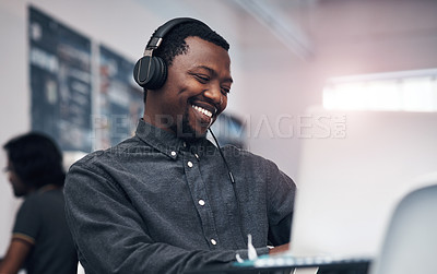 Buy stock photo Cropped shot of a handsome young businessman using a laptop while wearing headphones in a modern office