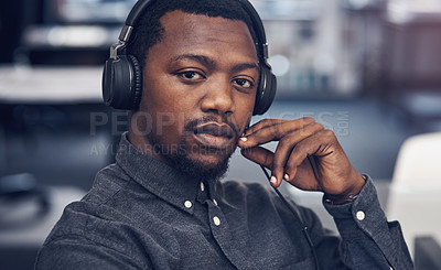 Buy stock photo Cropped portrait of a handsome young male architect wearing headphones while sitting in a modern office