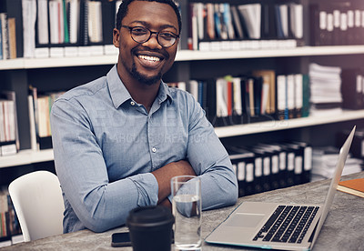 Buy stock photo Cropped portrait of a handsome young male architect smiling while working on a laptop in a modern office
