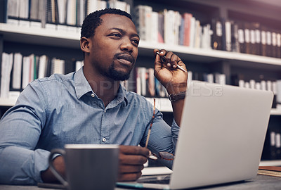 Buy stock photo Cropped shot of a handsome young male architect looking thoughtful while working on a laptop in a modern office